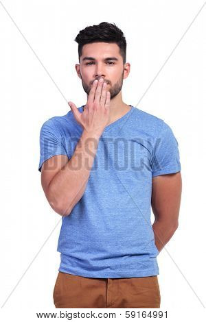casual young man covering his mouth with his hand on white background