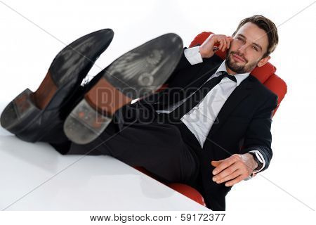 Successful satisfied businessman relaxing in his office leaning backed contentedly in his chair with his feet on the desk, over a white background