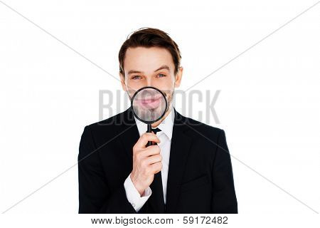 Happy businessman with a Big smile enlarged by the magnifying glass that he is holding in front of his mouth, isolated on white