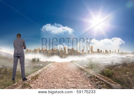Thinking businessman holding glasses against stony path leading to large urban sprawl under the sun