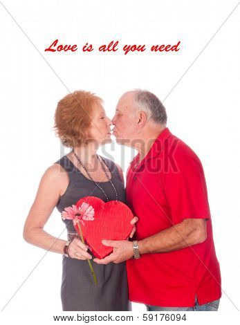 Love is all you need - an elderly couple embracing after the husband gave the wife flowers and chocolates