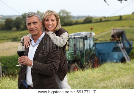 Couple with wine glass in front of vineyard