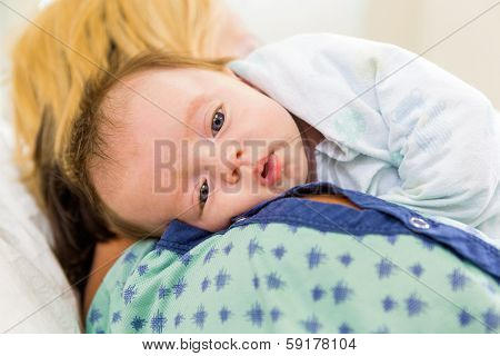 Closeup of cute newborn babygirl resting on mother's shoulder in hospital
