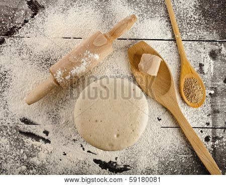 Wooden rolling pin with white wheat flour on the black surface table. top view