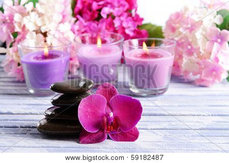 Beautiful colorful candles, spa stones and flowers,on color wooden background
