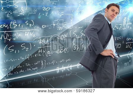 Stern businessman standing with hands on hips against math equation background