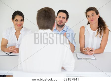 Panel of business people conducting job interview with male candidate