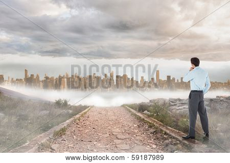 Thoughtful businessman with hand on chin against stony path leading to large urban sprawl
