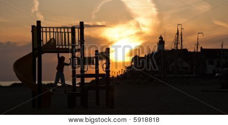 Child Playing At The Playground On The Beach In A Beautiful Sunset