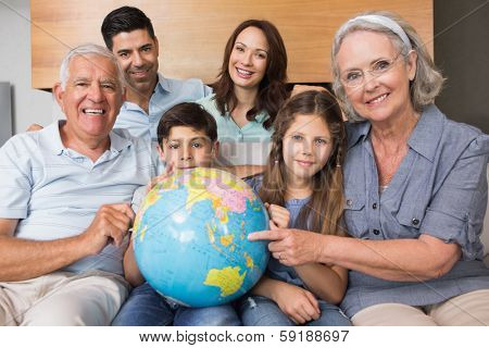 Portrait of an extended family sitting on sofa with globe in the living room at home