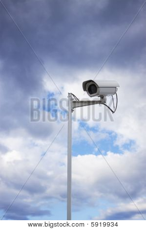 Surveillance Security Camera And Cloudy Sky