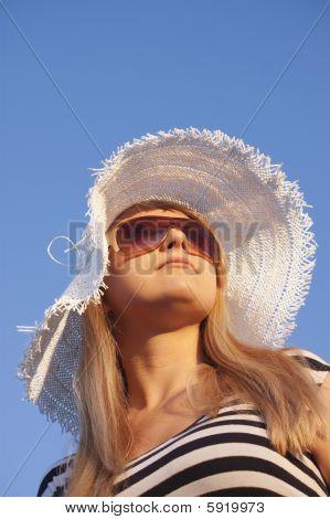 Joven sonriente a mujer rubia con sombrero blanco