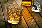 picture of scotch  - whiskey in glass with ice on wooden table - JPG