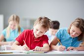 stock photo of schoolgirl  - Portrait of two diligent pupils drawing at lesson - JPG
