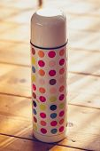 foto of thermos  - polka dotted Thermos On a Wooden Floor - JPG