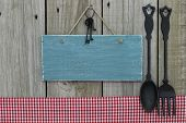 Blank antique blue sign with cast iron spoon and fork by red checkered tablecloth