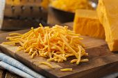 foto of shredded cheese  - Organic Shredded Sharp Cheddar Cheese on a Cutting Board