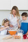 stock photo of flour sifter  - Children with mother baking cookies at counter top in kitchen - JPG