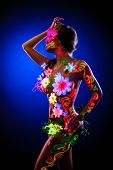 stock photo of uv-light  - Sexy slim woman posing with glowing flowers  - JPG