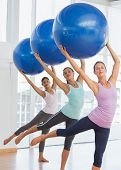 pic of pilates  - Happy fitness class and instructor doing pilates exercise with fitness balls in bright room - JPG