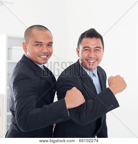 Southeast Asian business men celebrating success in office.