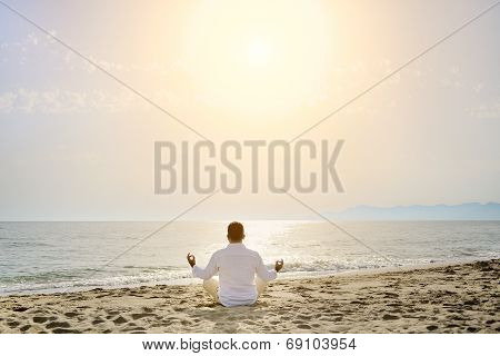 Healthy Lifestyle Concept - Man Doing Yoga Meditation Exercises On The Beach