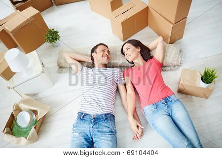 Happy young couple lying on the floor of new house and looking at one another
