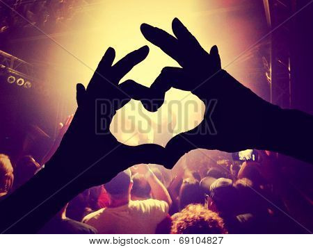 a crowd of people at a concert  with a heart silhouette on the singer