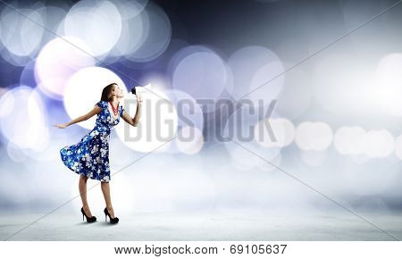 Young woman in blue dress talking in megaphone