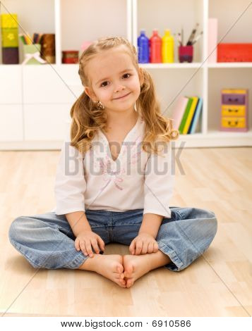 Happy Healthy Little Girl Sitting On The Floor