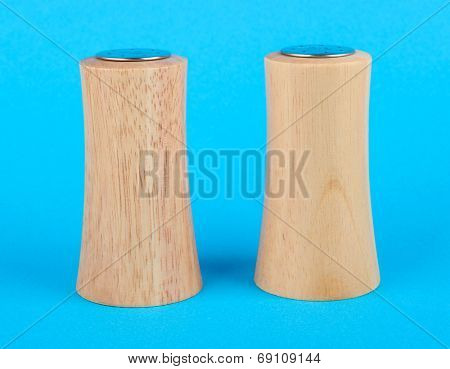 Salt and pepper shakers on color background