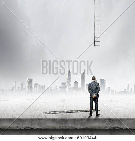 Rear view of businessman looking at broken ladder