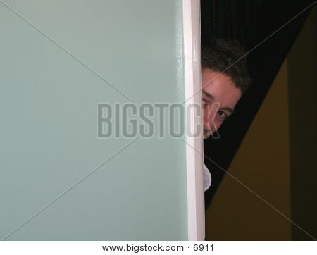 Young Boy Looking Round Door