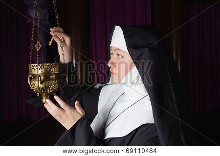 Nun in habit lighting a copper incense burner in church