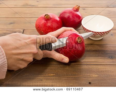 Female hands cutting a fresh pomegranate into sections