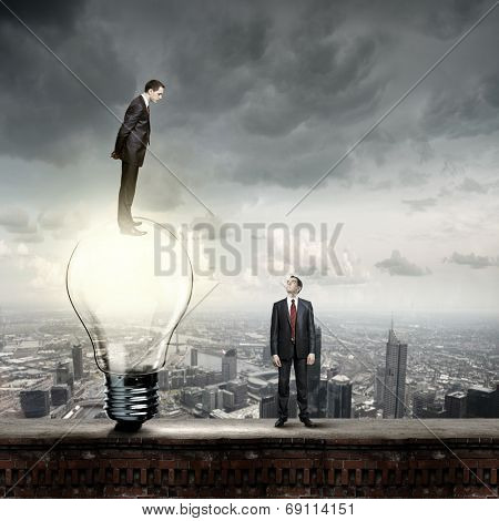 Businessman standing on top of light bulb and looking down