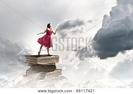 Woman in red dress standing on pile of books