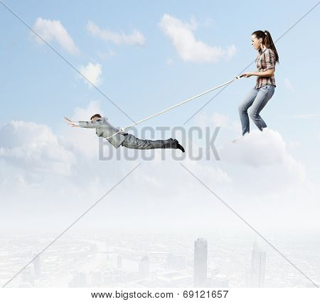 Woman holding on lace businessman trying to escape