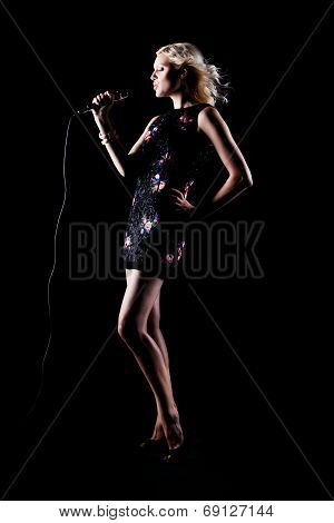 Full-length portrait of pretty beautiful singing woman with microphone. Singer. Karaoke song