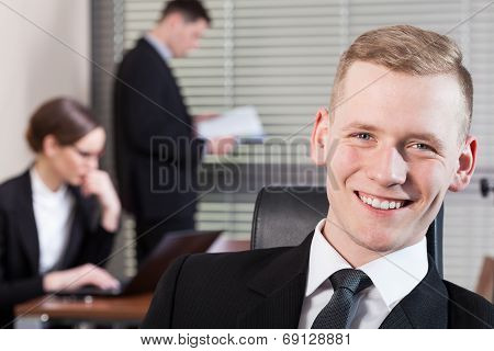 Smiling Businessman And His Co-workers