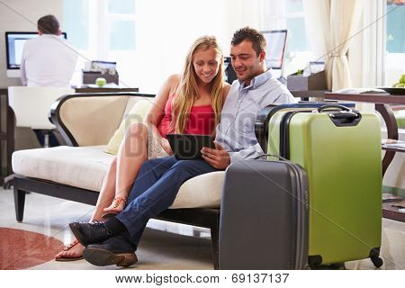 Couple Sitting In Hotel Lobby Looking At Digital Tablet