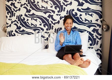 Businesswoman Video Conferencing On Digital Tablet In Hotel