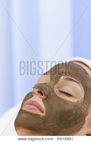 Young Woman Having Chocolate Face Mask Facial At Health Spa