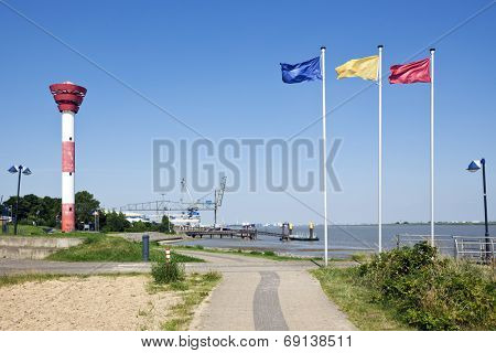 Lighthouse and piers at Nordenham, flagpoles with flags in foreground