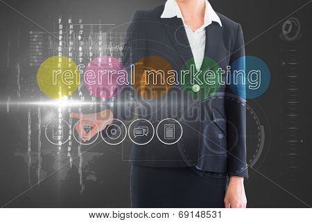 Businesswoman touching the words referral marketing on interface against grey vignette