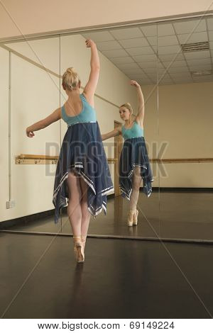 Beautiful ballerina dancing in front of mirror in the dance studio