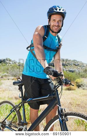 Fit cyclist riding in the countryside smiling at camera on a sunny day