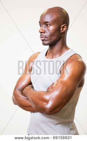 Serious muscular man with arms crossed looking away over white background