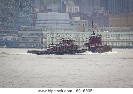 NEW YORK - MAY 27: Tugboats Robert E. McAllister and Resolute trail the USS Oak Hill (LSD 051) after departing Pier 92 at the end of Fleet Week NY. Image contains visible atmospheric distortion.