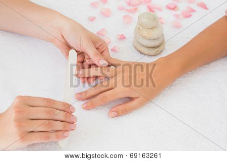 Close up of beautician filing female client's nails at spa beauty salon
